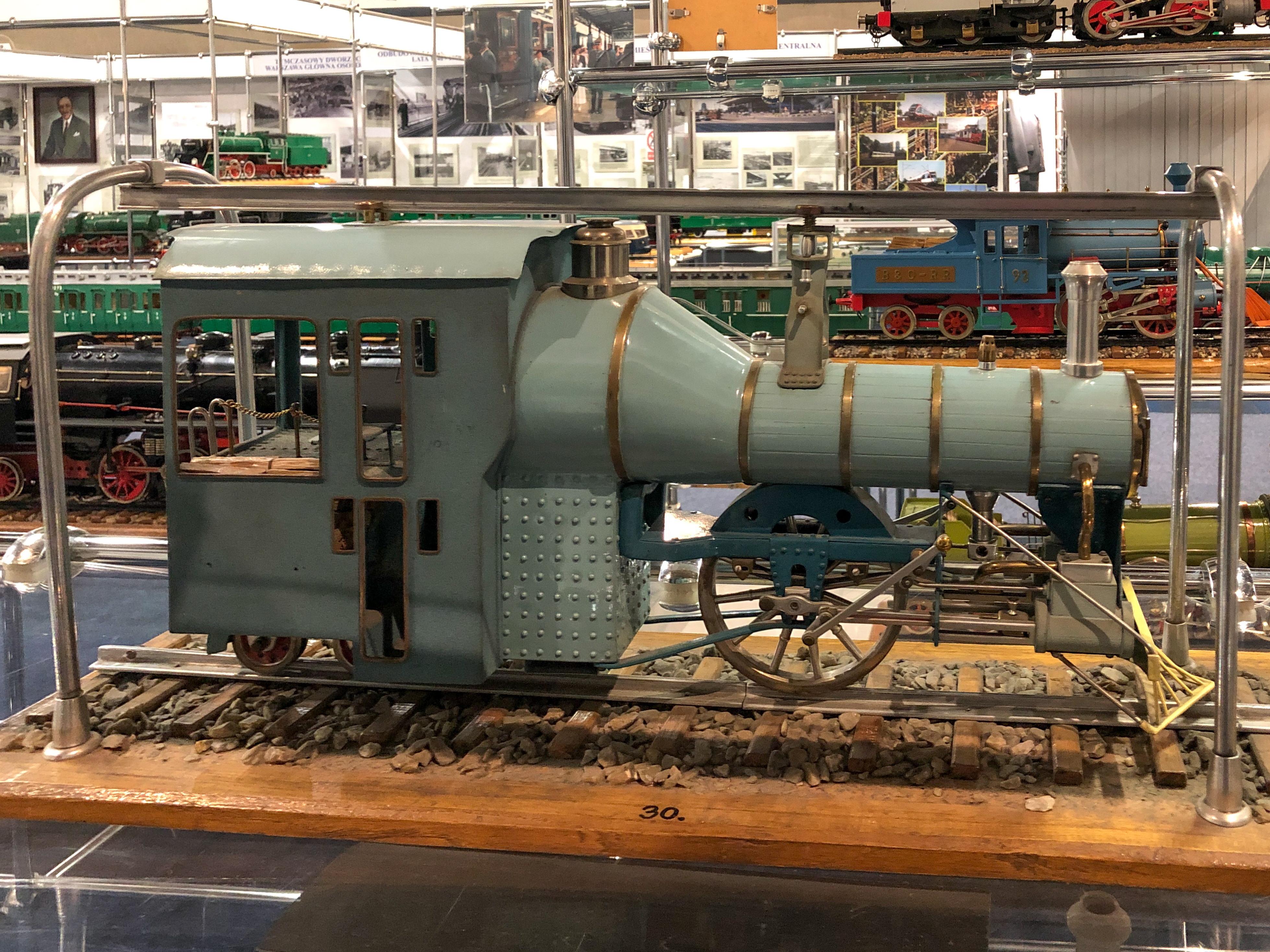 A model of a steam locomotive running on a single rail below, and supported by one above. The front is to the right.